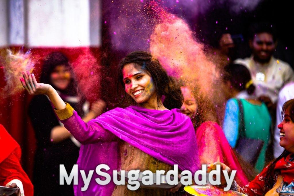 Auf dem Bild sieht man eine Frau die mit Farben um sich wirft. Sie ist glücklich. Viele Menschen sind auf dem Bild zu sehen. Sehr Farben froh. Ein traditionelles Fest. Für so manchen vielleicht ein Kulturschock?